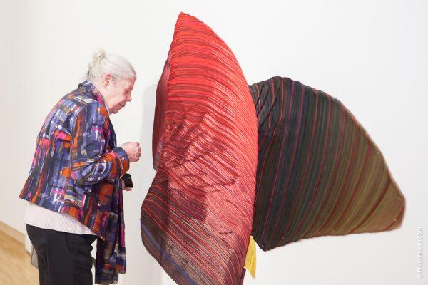 Vrouw bij kunstwerk van grote kussens