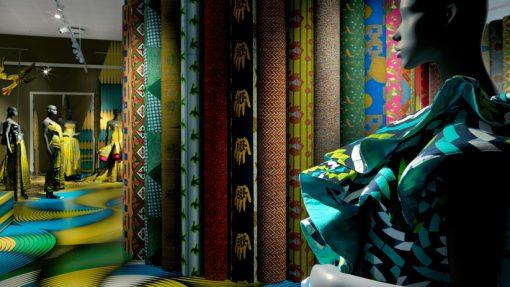 Paspop met kleurrijk dessin en de achtergrond verschillende Vlisco stoffen