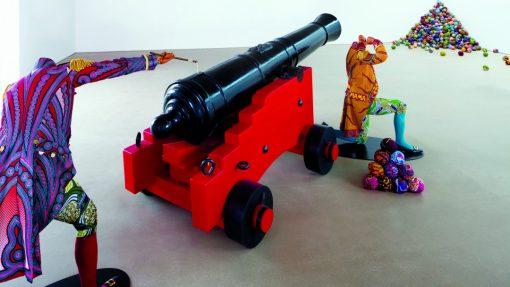 Een kanon en twee figuren die samen kanonskogels afvuren naar een hoek van de zaal. Daar is een grote berg met kanonskogels van Vlisco-stoffen te zien.