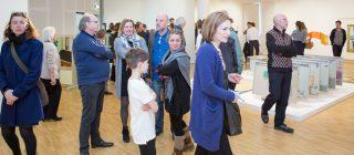 Groep mensen die aandachtig door expositie loopt.