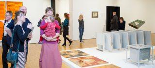 Bezoekers staan in een kunstruimte te praten.
