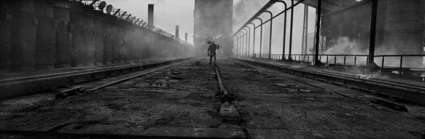 Zwart wit foto van mijnwerker met schep op de rug, gemaakt in Duinkerke