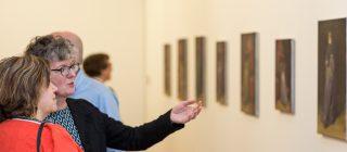 Bezoekers die staan voor een wand met kunst.