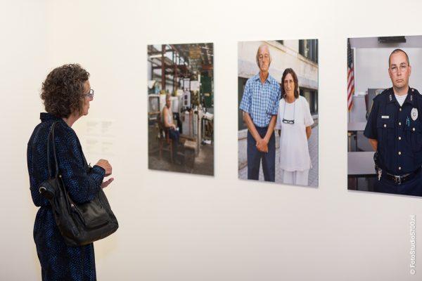 Vrouw staand voor drie portretfoto's