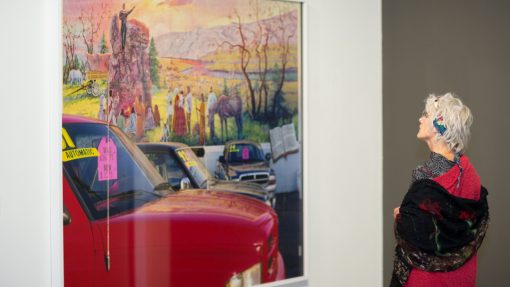 Vrouw staand voor kunstwerk met auto's