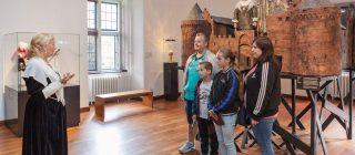 Groepje mensen krijgt uitleg van medewerker Museum Helmond.