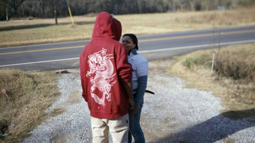 Jongen met capuchon en meisje bij een weg