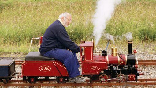 Jan Dirk van der Burg op een rode modelbouw locomotief