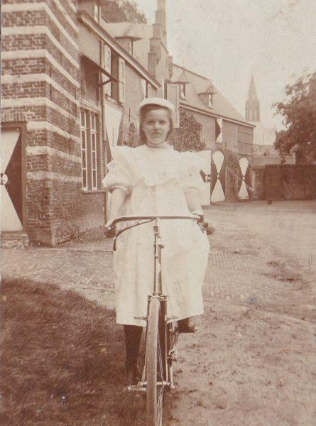 Oude foto van jonkvrouw Emelie op fiets voor het kasteel