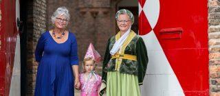 Drie personen die feestelijk verkleed zijn.