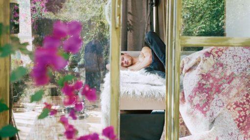Inkijk door glazen deuren naar man die op een bed ligt